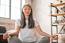 Relaxed Mature Caucasian Woman Meditating At Home
