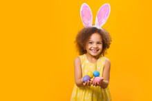 An African Girl In Sunny Orange Dress With Rabbit Ears On Her Head With Painted Eggs In Her Hands On A Yellow Background
