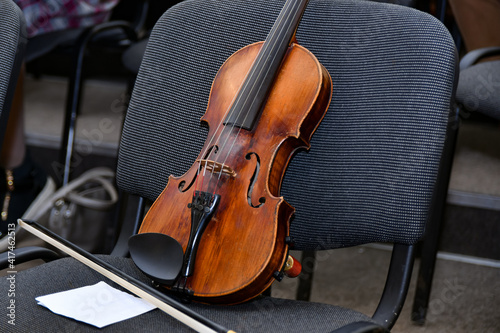 Carta da parati A violin with a bow and notes stands on a chair in the middle of an empty concert hall