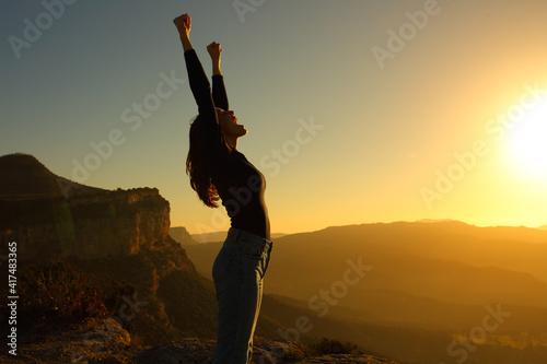 Fotografia, Obraz Profile of a woman screaming raising arms celebrating sunset