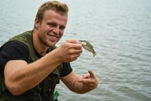 Man Holding Really Small Largemouth Bass