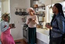 Black Women Friends Drink Tea In Kitchen During Self Care Weekend Retreat