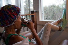 Woman Drinks Tea While Meditating And Looking Out Window
