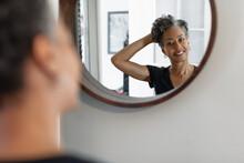 Pretty Black Mature Woman Checks Natural Hair In Mirror At Home