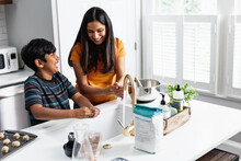 Indian Mom And Son Washing Hands In Kitchen