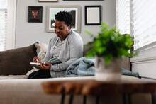 African American Woman Writes In Her Journal At Home In Living Room