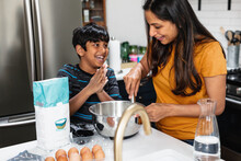 Indian Mother And Son Baking In Kitchen, Having Fun