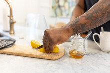 Black Man With Tattoos Slices Fruit For Tea Drink