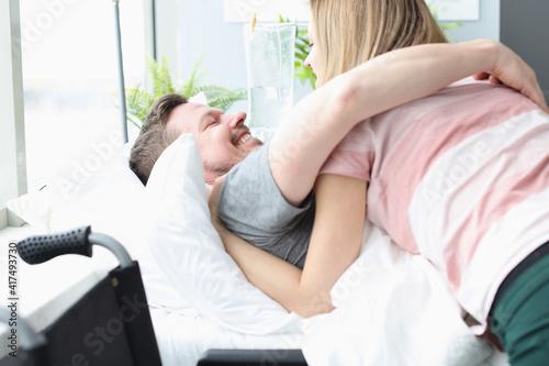 Fototapeta Joyful man hugs woman on hospital bed obraz