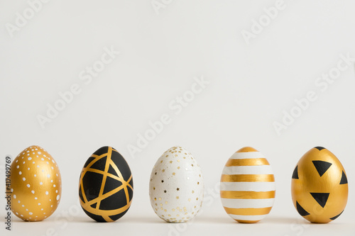Fototapeta Easter golden decorated eggs stand in a row on white background. Minimal easter concept. Happy Easter card with copy space for text. Top view, flatlay. obraz