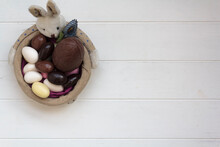 Top View Of Easter Bunny Basket With Chocolate Almond Eggs On White Wooden Table With Copy Space