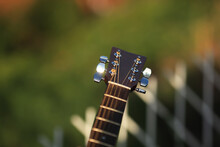 Guitar Tuner. Wooden Guitar On A Natural Blurred Background. Guitar Tuning. The Guy Tunes The Guitar.