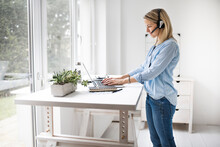Businesswoman Working At Ergonomic Standing Workstation