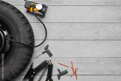 Car fitting service concept flat lay background with copy space. Car tyre, car jack, air pump and wheel repair kit on the gray background.