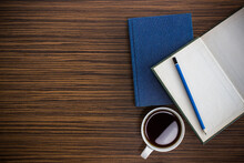 Pencil With Notebook And Coffee On A Wooden Table
