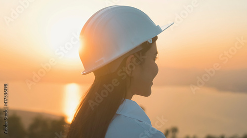 a woman engineer is putting a protective helmet on her head at sunset. - fototapety na wymiar