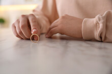 Woman Holding Wedding Ring At Table Indoors, Closeup. Divorce Concept