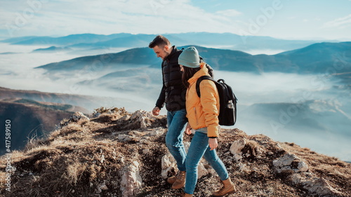 Fototapeta happy couple man and woman tourist at top of mountain during a hike in summer