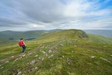 A Hiker Walking Towards Creag An Fheadain From Sron Chona Choirein In The Scottish Highlands, UK Mountain Landscapes.