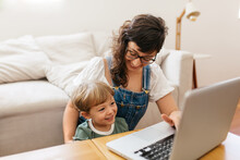 Happy Mother And Son With Laptop At Home