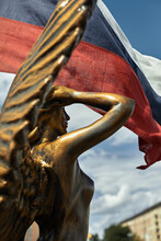 Antique Golden Statue Angel Figurehead Decorative Rostrum Ship Against The Background Of The Russian Flag