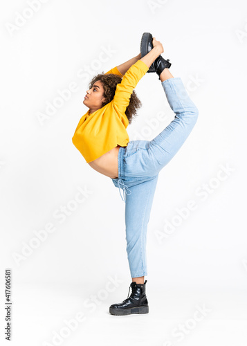 Fototapeta premium Young African American woman dancing over isolated white background
