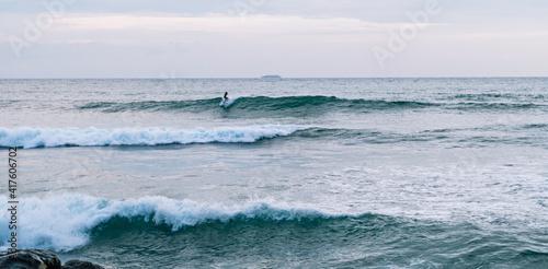 Fototapeta Surfer na fali, na tle oceanu, skał i wzburzonej wody. obraz