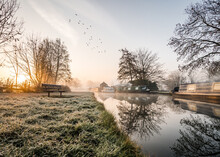 Stunning Old Canal House Boats Landscape Sunrise In Countryside With River And Single Lone Wooden Bench. Frost On Grass Reflection Of Trees And Vessels Chimney Smoke In Still Calm Water Birds In Sky.