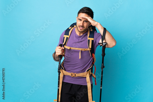 Fototapeta Young caucasian man with backpack and trekking poles isolated on blue background looking far away with hand to look something obraz