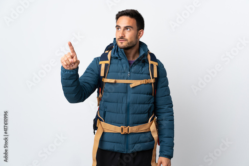 Fototapeta Young mountaineer man with a big backpack isolated on white background touching on transparent screen obraz