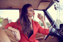 Beautiful Young Vogue Woman In Red Suit Sitting In Retro Car Using A Perfume.