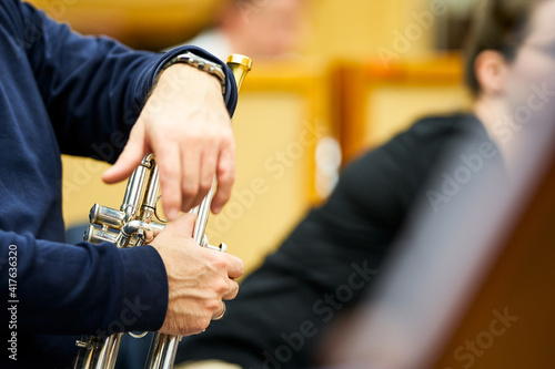 Obraz Trumpeter's hands resting on the trumpet during a break in the rehearsal. - fototapety do salonu