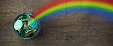 Pot With Gold Coins And Rainbow On Wooden Background. St Patrick's Day Celebration.