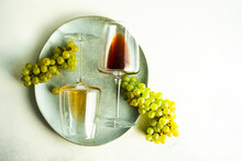Glasses Of Red And White Wine Lying On A Plate With Green Grapes
