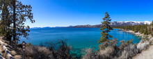 A Breathtaking Panoramic Shot Of The Vast Deep Blue Lake Water And Lush Green Trees With Snow Capped Mountains And Blue Sky At Lake Tahoe Nevada State Park In Incline Village Nevada