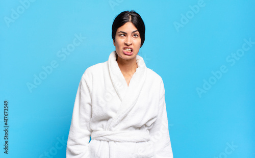 Photo young hispanic woman looking goofy and funny with a silly cross-eyed expression, joking and fooling around