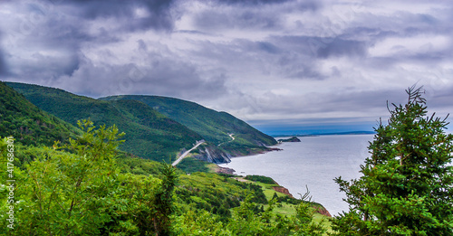 The Cabot Trail winds it's way through the green forested highlands along the ocean shoreline of Cape Breton Island in Nova Scotia Canada Fototapet