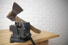 The General Plan On A Wooden Table Top Is Set With A Black Vise With A Screw Grip And A Cast-iron Frame, In A Machine Shop. The White Brick Background Is Blurred.