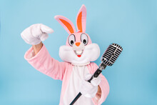 Happy Funny Kid Boy Or Girl Singer Or Vocalist Sings Song To Retro Vintage Classic Microphone. Easter Bunny Or Rabbit Or Hare Celebrates Happy Easter Isolated On Blue