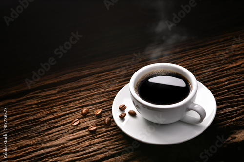 Top view of cup of coffee with smoke and coffee beans on old wooden background. © amenic181