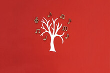 Tree, The Crown Of A Tree Made Of Musical Notes On A Red Background. Creation Of Musical Compositions. Teamwork.