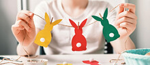 Banner With DIY Easter Home Decor. Happy Boy Make Garland Of Colored Paper, Twine And Pom-poms. Selective Focus