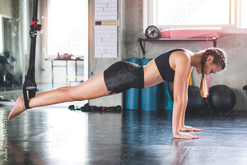 Fotografija Athlete sporty woman doing exercise with fitness trx straps to strengthen his ab