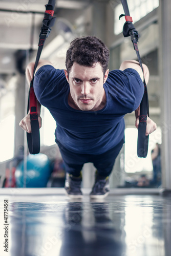 Athlete sporty man doing exercise with fitness trx straps to strengthen his abdominal muscle in gym © weerayut