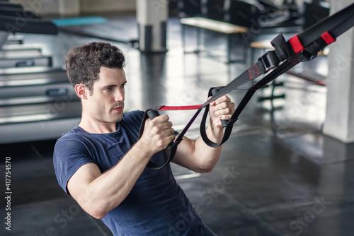 Slika na platnu Athlete sporty man doing exercise with fitness trx straps to strengthen his abdo