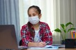 A brunette girl in a medical mask, dressed in a red shirt sitting at home studying, writes homework, communicates online.