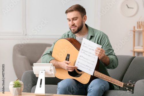 Fotografia Young man taking music lessons online at home
