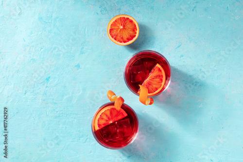 Fototapeta Orange cocktails, overhead flat lay shot on a blue background with a place for text obraz na płótnie