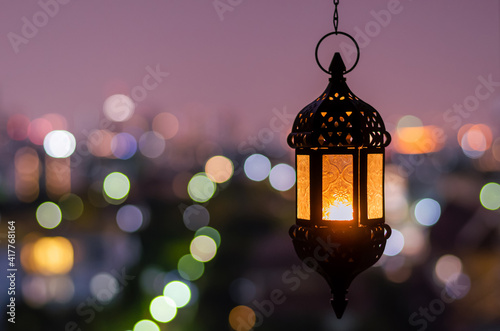 Fototapeta Hanging lantern with night sky and city bokeh light background for the Muslim feast of the holy month of Ramadan Kareem. obraz