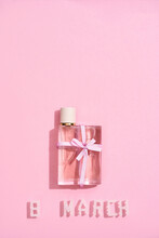 Vertical Shot Of A Perfume Bottle With Bow And Text 8 MARCH Made With Two Little Roses And White Plastic Letters Over Pink Background